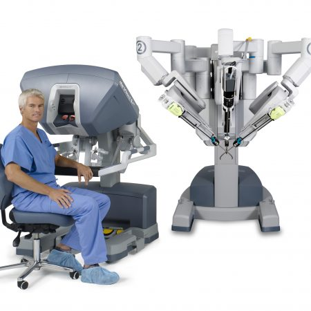 A surgeon sitting by the surgical console which controls the Da Vinci robot which allows for greater accuracy and precision.